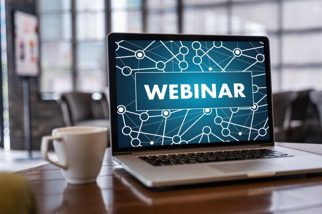 Laptop shows webinar virtual event on screen.